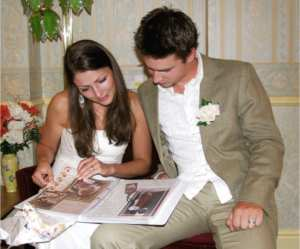 the bride and groom looking through their wedding day scrapbook